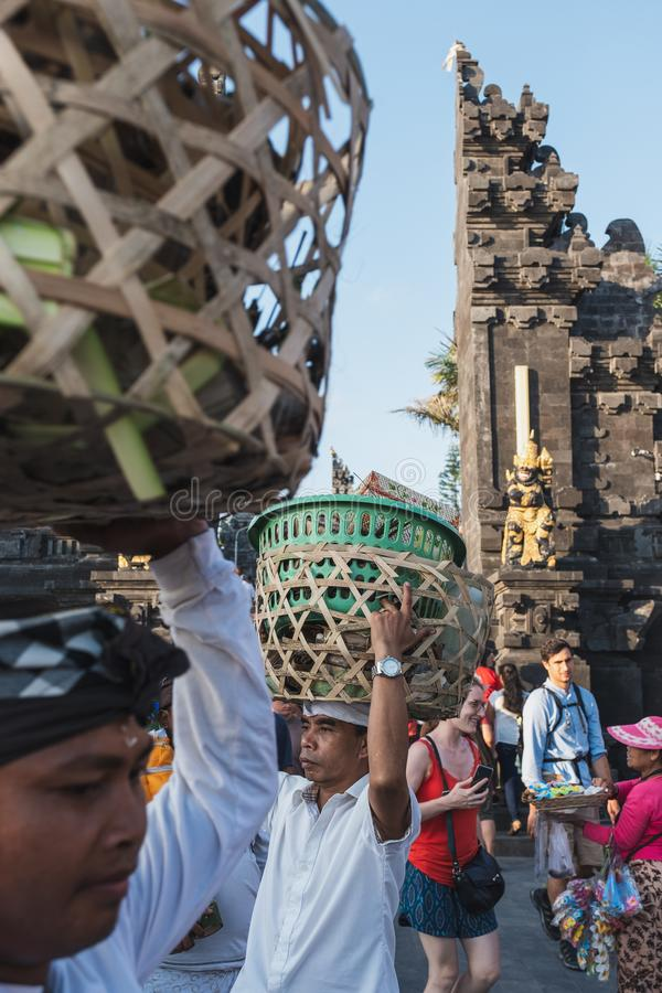 Bali, Indonesia - Sep 09 2018 : Balinese carry basket on head of traditional lifestyle in Hindu Temple. Bali, Indonesia - Sep 09 2018 : Balinese carry basket on royalty free stock photos