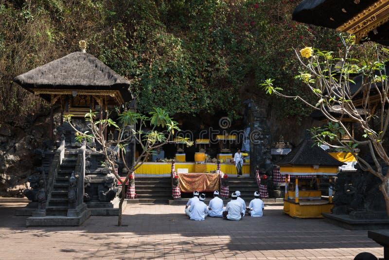 Sacred ceremony in Goa Lawah Bat Cave, Bali, Indonesia. BALI, INDONESIA - SEP 26: Men in white traditional clothes take part in sacred ceremony in Goa Lawah Bat stock photography