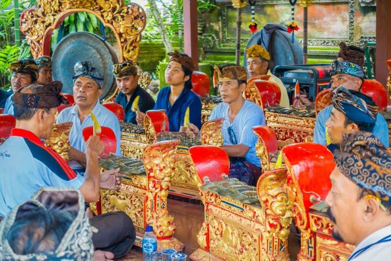 BALI INDONESIEN - APRIL 05, 2017: Oidentifierat folk som spelar några musikinstrument inom av en byggnad i arkivbilder