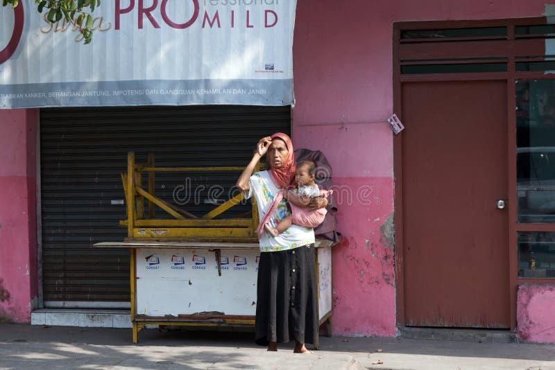 BALI INDONESIEN - AUGUSTI 30,2012: Ung kvinna med ett småbarn royaltyfria foton