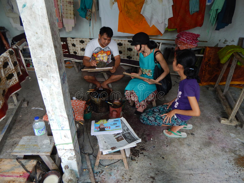 BALI INDONESIEN - CIRCA 2014: En batikseminariumarbetare visar en turist hur man gör en battic design på ett stycke av kanfas när arkivfoton