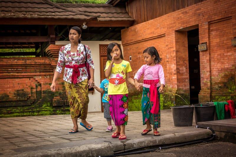BALI INDONESIEN - DECEMBER 5, 2017: Balinesebarn i traditionell kläder som går med modern i den Tirta Empul templet arkivfoto