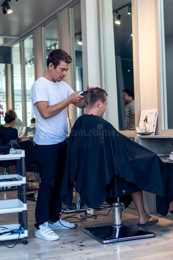 BALI INDONESIEN - JUNI 2, 2017: Hårstylisten på barberaren shoppar på den Bali ön arkivfoto