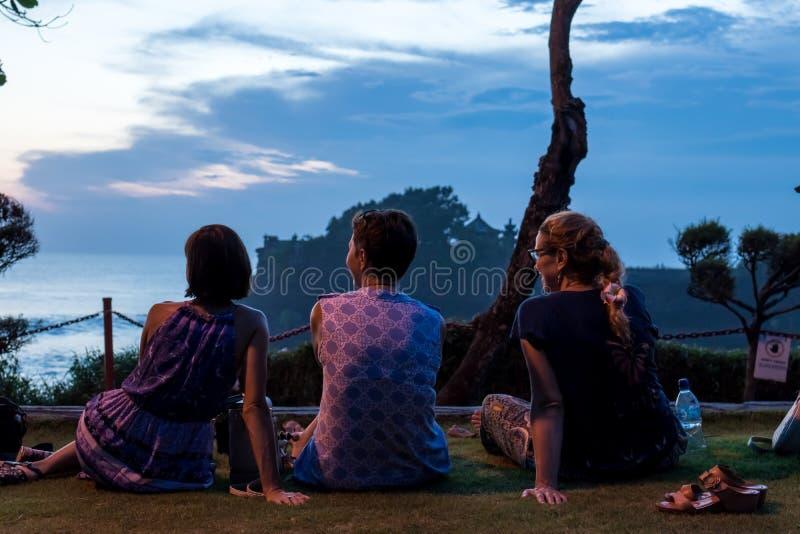 BALI INDONESIEN - MAJ 4, 2017: Tre kvinnor på en bakgrund av den Pura Tanah lotttemplet, Bali ö, Indonesien skjuten solnedgångtid royaltyfria foton
