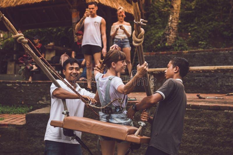 BALI INDONESIEN - NOVEMBER 25, 2017: Två män som hjälper en flicka att sitta ner på gungor på klippan Tropisk Bali ö arkivbild