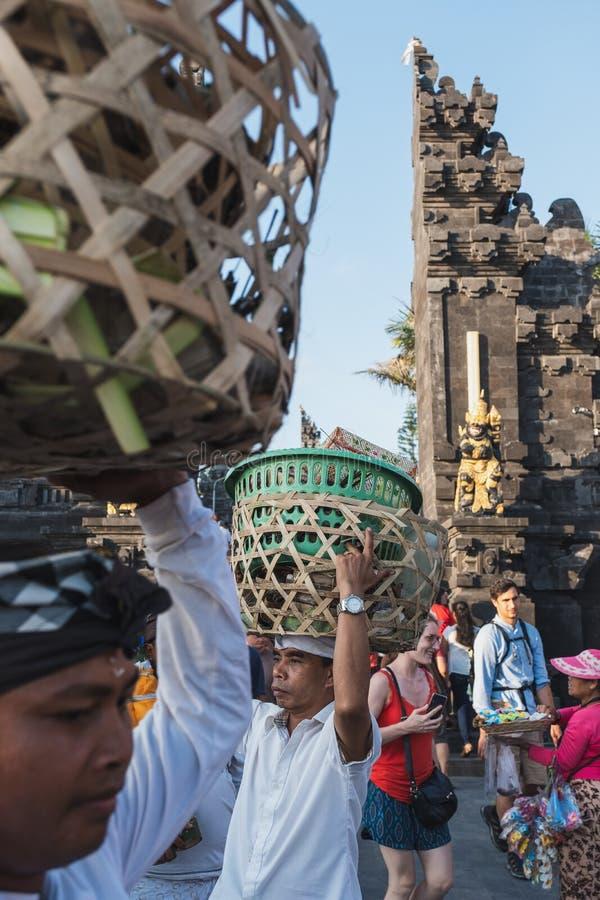 Bali Indonesien - September 09 2018: Balinesen bär korgen på huvudet av den traditionella livsstilen i hinduisk tempel royaltyfria foton