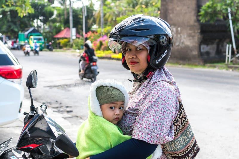 BALI INDONEZJA, CZERWIEC, - 2, 2017: Portret balijczyk matka z jej dziećmi siedzi na motocyklu w rękach fotografia stock