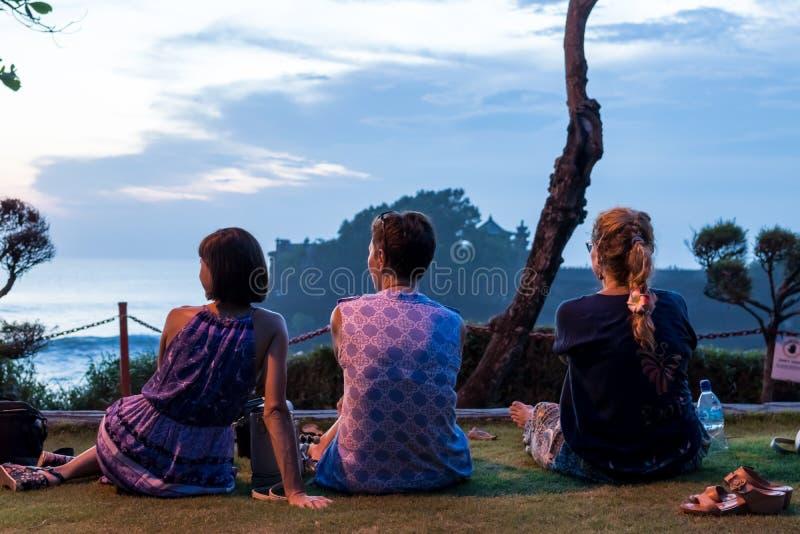 BALI INDONEZJA, MAJ, - 4, 2017: Trzy kobiety na tle Pura Tanah udziału świątynia, Bali wyspa, Indonezja ujawnienia zawodnik bez s fotografia stock