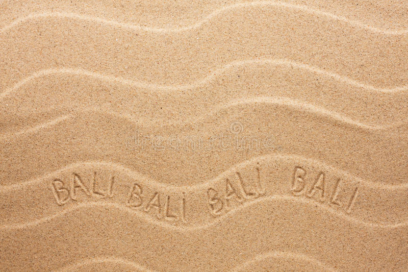 Bali inscription on the wavy sand. As background stock image