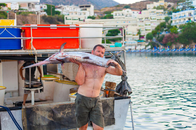 Bali, Island Crete, Greece, - June 30, 2016: Man is a fisherman carries a big fish sawfish. After successful fish catch from the fishing boat stock photo