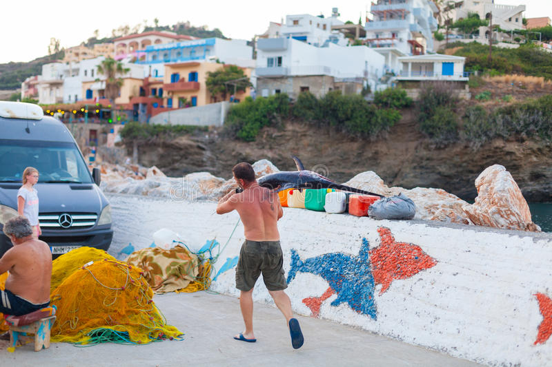 Bali, Island Crete, Greece, - June 30, 2016: Man is a fisherman carries a big fish sawfish. After successful fish catch from the fishing boat stock photos