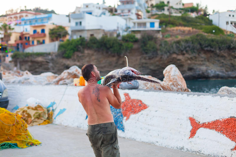 Bali, Island Crete, Greece, - June 30, 2016: Man is a fisherman carries a big fish sawfish. After successful fish catch from the fishing boat stock photography