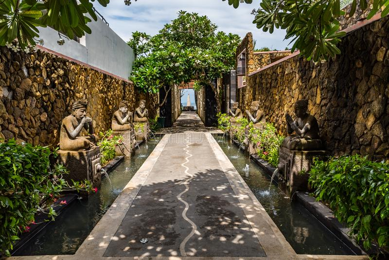Bali Pathway lined with traditional statues and plants. On a hot and sunny day stock images