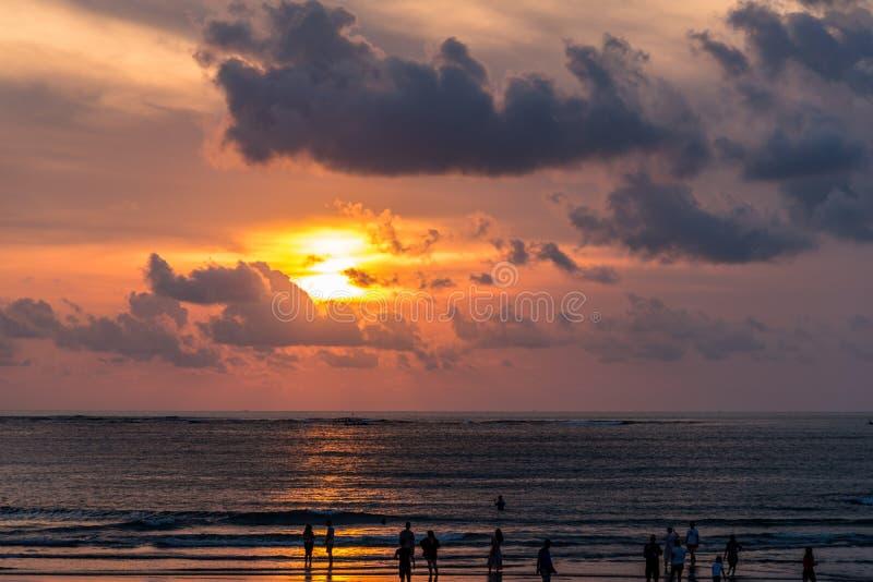 Bali solnedgång med folk på stranden royaltyfri fotografi