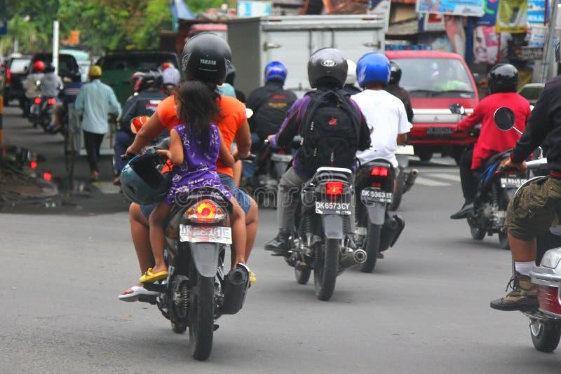bali Styczeń 2019 Niebezpieczna jazda motocykl Transport dzieci bez hełma Dziewczyna jedzie z jej matką dalej zdjęcia stock