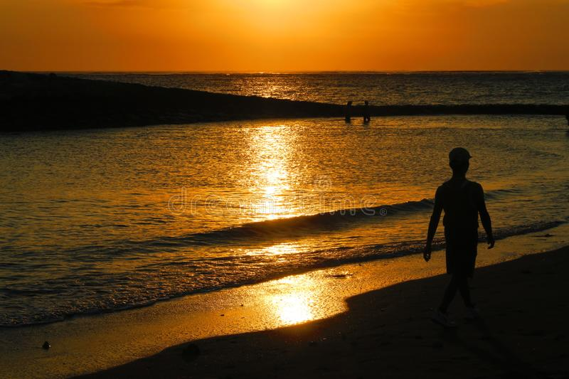Bali yellow sunset or sunrise silhouette of man walking stock photography