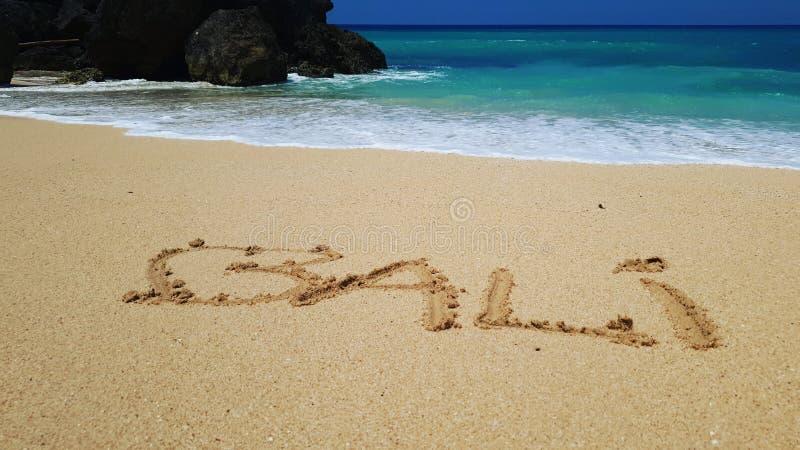 Bali in zand op strand wordt geschreven dat royalty-vrije stock fotografie