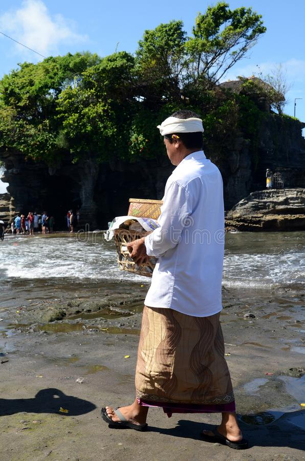 Balijczyka mężczyzna przynosi jego ofiary uczęszczać modlitwę przy Tanah udziału świątynią, Bali zdjęcie royalty free
