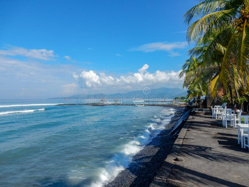 Balinese beach with black sand, palm trees and beach cafe tables stock images