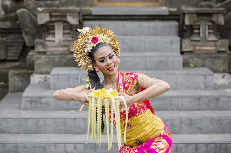 Balinese dancer dancing while carrying flower stock photo