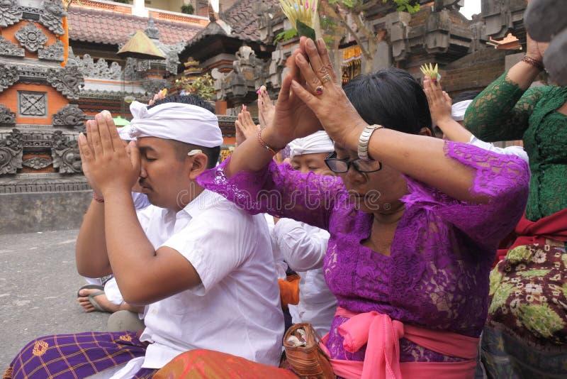 Balinese family celebrating Galungan Kuningan holidays in Bali Indonesia. Balinese family celebrating Galungan Kuningan holidays in a family temple in Ubud Bali royalty free stock images