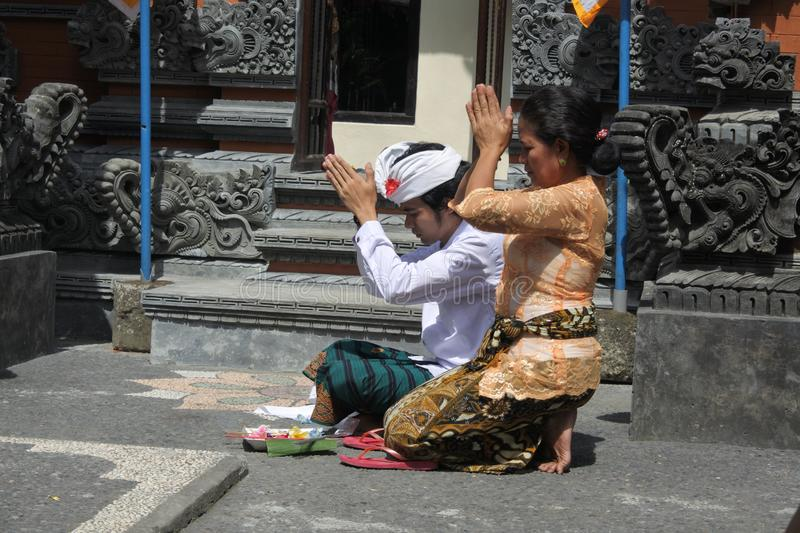 Balinese family celebrating Galungan Kuningan holidays in Bali Indonesia. Balinese family celebrating Galungan Kuningan holidays in a family temple in Ubud Bali stock image