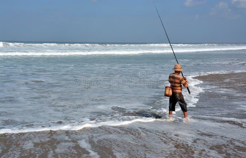 Balinese Fisherman Surf Casting on Legian Beach. stock photos