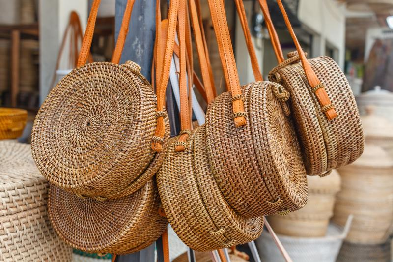 Balinese handmade rattan woven round shoulder bags with leather handles at a street shop. Bali, Indonesia. stock photos