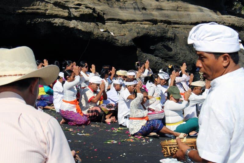 Balinese Hindoese mensen die rond iconische Pura Tanah Lot bidden royalty-vrije stock afbeelding