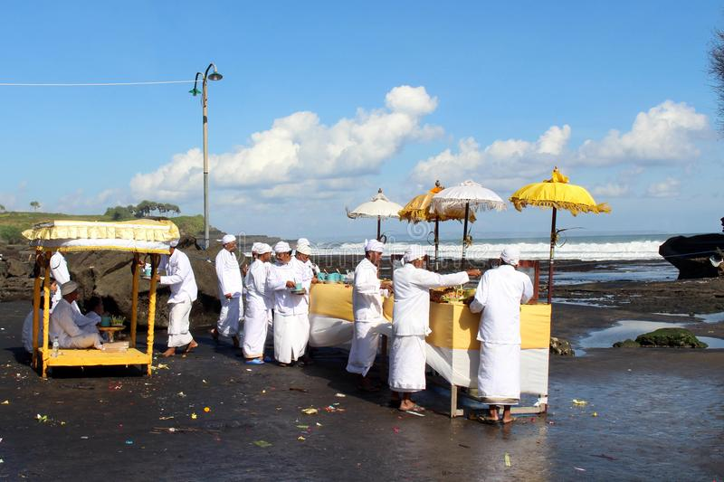 Balinese Hindoese priesters die rond iconische Pura Tanah Lot bidden stock foto's