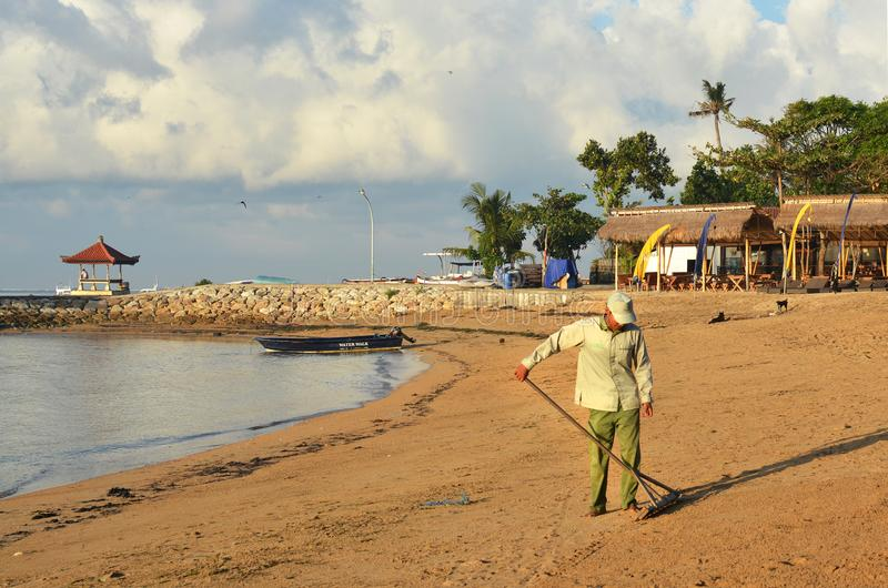 Balinese man grooms beach at Sanur, Bali in morning, Indonesia stock images