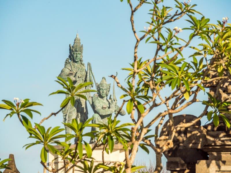 Balinese standbeelden met bomen in de voorgrond, Benoa Bali stock foto's