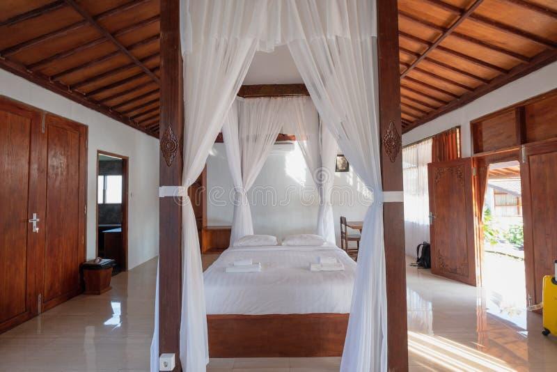 Balinese stijl van de architectuur de houten slaapkamer met gordijn van tropische villa stock foto