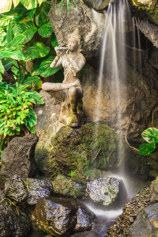 Balinese Waterfall. Waterfall with Balinese statue and lush greenery royalty free stock photography