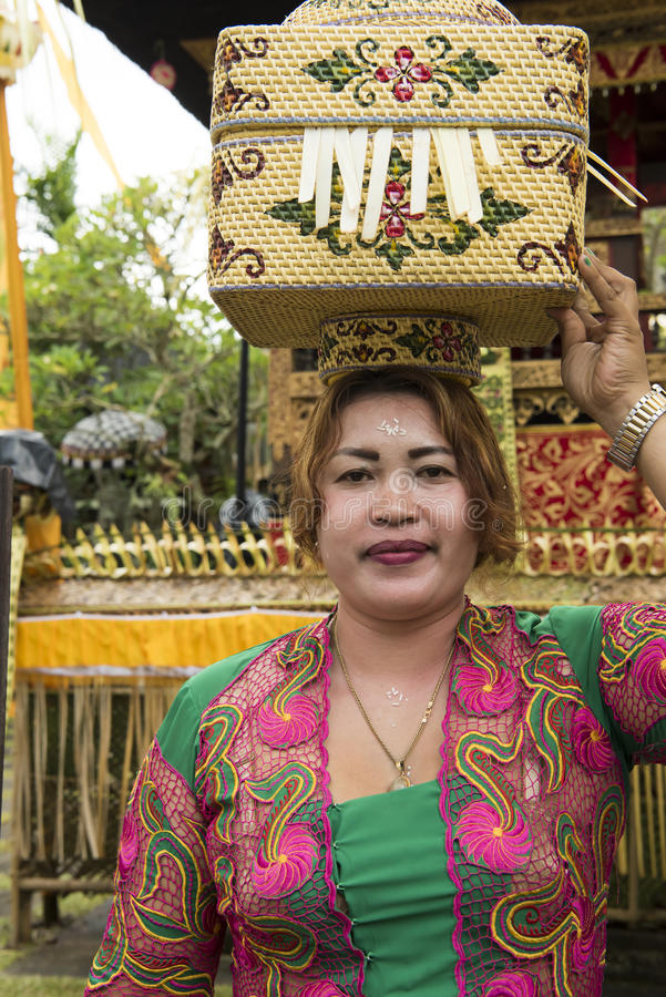 Balinese woman bringing offerings to temple stock photography
