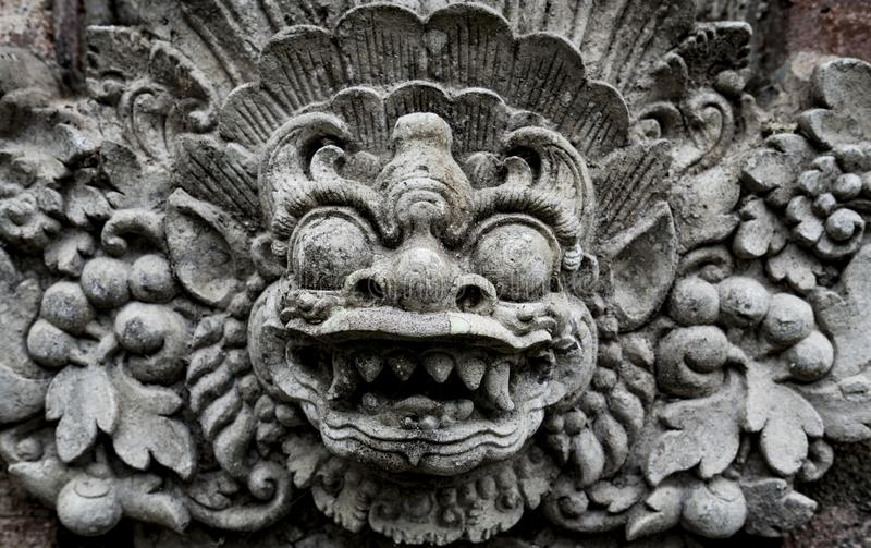 Balinesedemon som snidas i sten arkivfoto