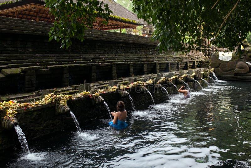Balinesefolk som ber i heligt vårvatten av den sakrala pölen på Pura Tirta Empul Temple, Tampaksiring, BALI, INDONESIEN - fotografering för bildbyråer