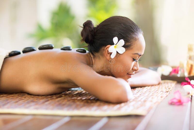 Balinesefrau, die Warmsteinmassage im Badekurortsalon hat stockbilder