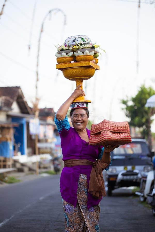 Balinesefrau mit cild lädt das Angebot des Lebensmittels im hölzernen Glas auf ihrem Kopf stockbilder