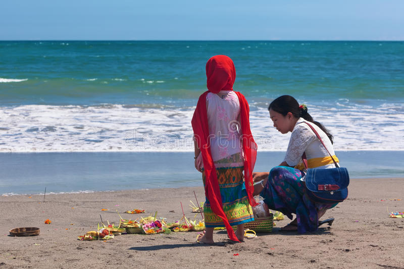 Balinesefrau mit Kind auf Ozeanstrand lizenzfreies stockfoto