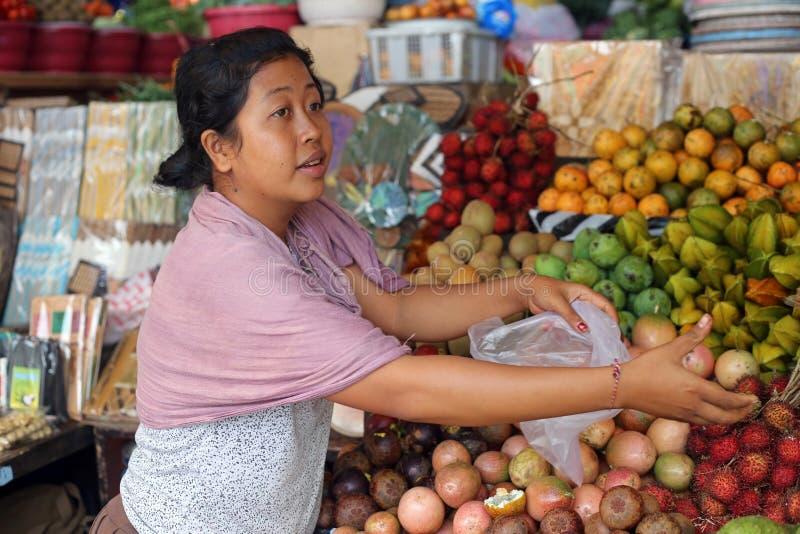 Balinesekvinna som säljer tropisk frukt i en marknad i Bali arkivfoto