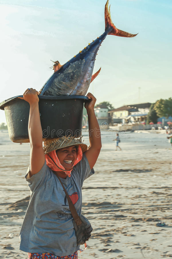Balinesen bär fiskar i handfat royaltyfri bild