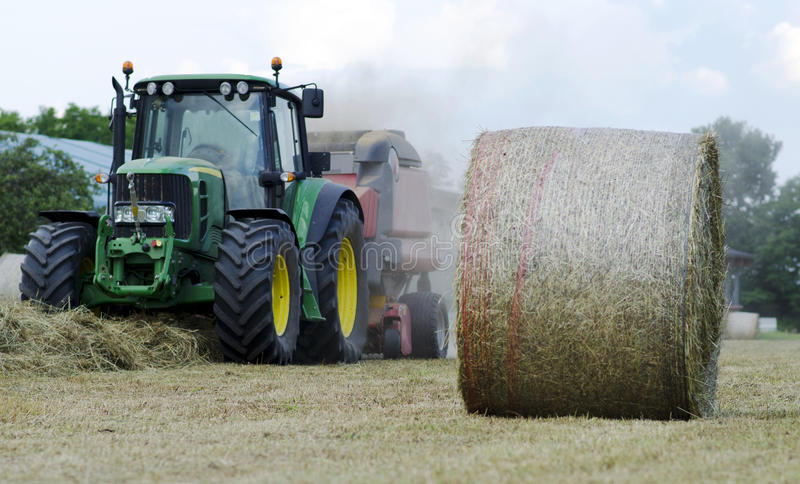 Baling hay in field. Tractor with baling machine in a field royalty free stock images
