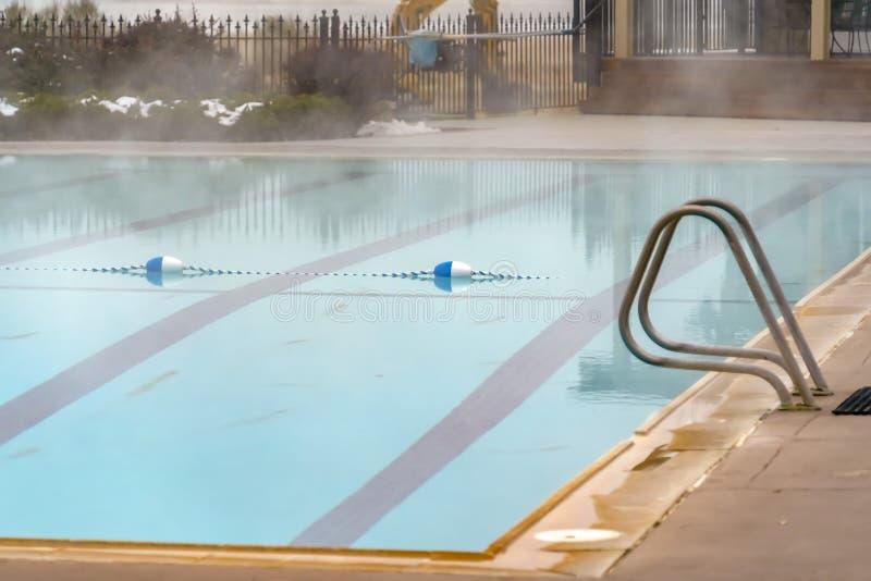 Balise bleue et blanche et marqueur de ruelle de corde flottant sur une piscine extérieure images stock
