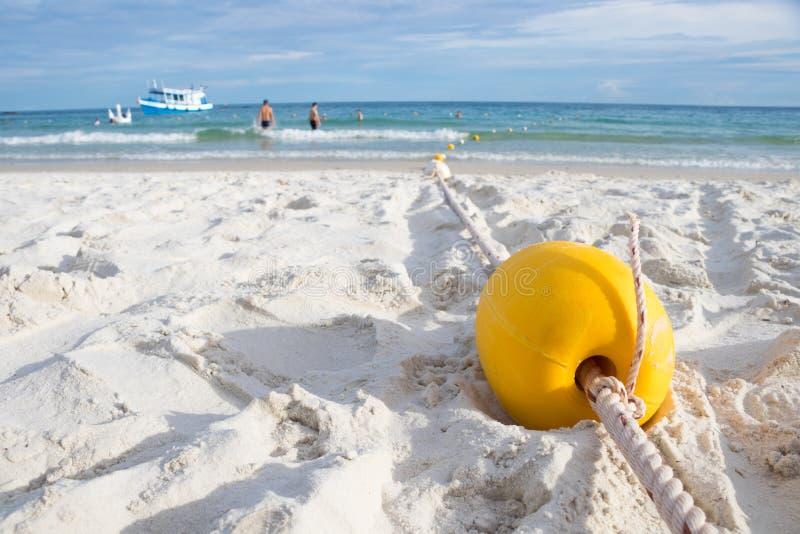 Balise jaune sur la plage pour faire le secteur de sécurité de natation pour des touristes images libres de droits