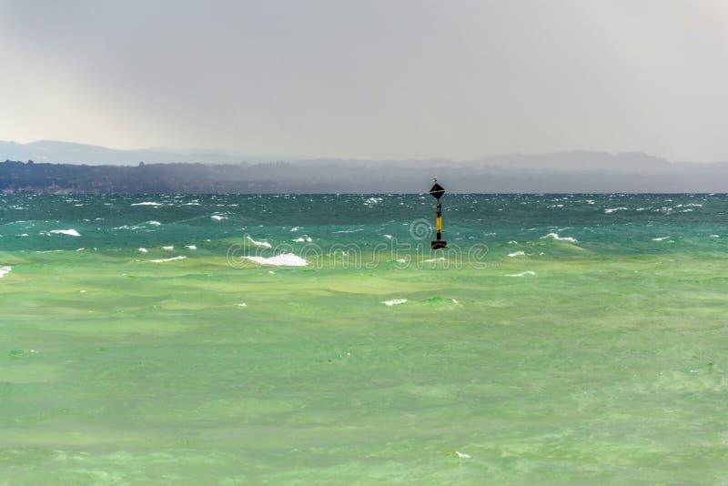 Balise noire et jaune dans les vagues vertes bleues turbulentes sur le lac Lago di Garda, temps venteux, nuageux, brumeux, Sirmio photographie stock libre de droits