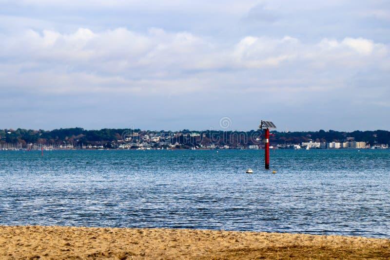 Baliza posta solar no mar com a cidade no horizonte imagens de stock royalty free