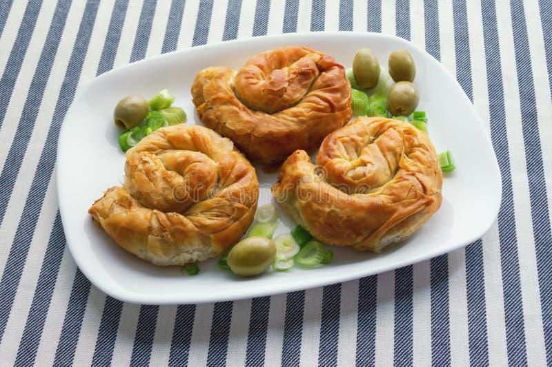 Balkan cuisine. Burek - popular national dish. Three round burek on white plate royalty free stock photography