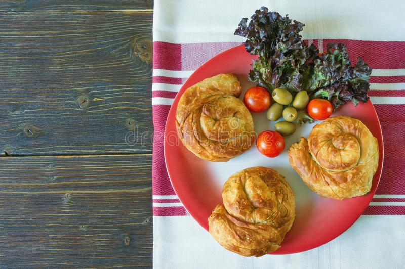 Balkan cuisine. Bureks - popular national dish - on red plate. Flat lay, free space for text. Balkan cuisine. Bureks - popular national dish - on red plate. Dark stock photos