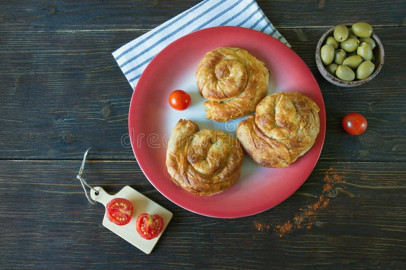 Balkan cuisine. Bureks - popular national dish - on red plate.  Flat lay. Free space for text. Balkan cuisine. Bureks - popular national dish - on red plate stock photography